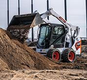 Operator Using Bobcat S590 Skid-Steer Loader With Bucket Attachment To Dump Dirt On Pile