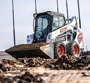 Bobcat S590 Skid-Steer Loader Carrying Dirt Across Jobsite