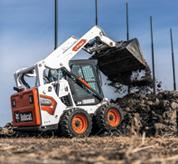 Operator Using Bobcat S590 Skid-Steer Loader With Bucket Attachment To Dump Dirt Onto Pile