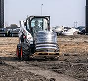 Operator Using Bobcat S590 Skid-Steer Loader With Pallet Fork Attachment To Move Material On Jobsite