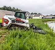 Landscaper Using Bobcat T550 Compact Track Loader With Brushcat Attachment To Clear Brush Along Pond