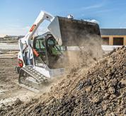 Operator Using Bobcat T595 Compact Track Loader With Bucket Attachment To Dump Dirt On Pile
