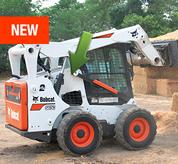 Bobcat S650 skid-steer loader lifts a bail of hay onto a pile with bale forks.