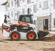 R-Series Skid-Steer Loader Moving Dirt With Bucket