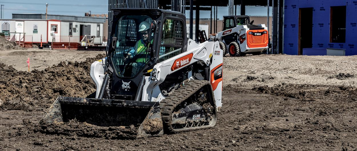 Construction Worker In A Bobcat T62 Compact Track Loader Moving Dirt With Bucket Attachment On Residential Jobsite With S62 Skid-Steer Loader Working In Background