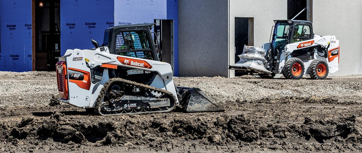 'Operators Use Bobcat T62 Compact Track Loader With Bucket Attachment and S62 Skid-Steer Loader With Pallet Fork Attachment On Jobsite