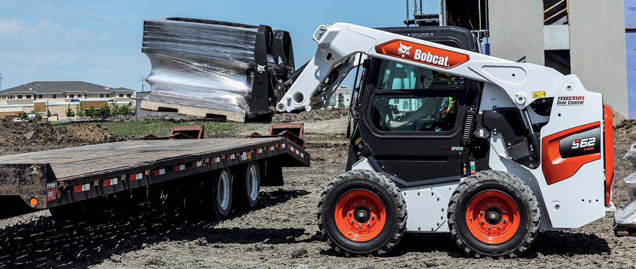 Construction Worker Using Bobcat S62 Skid-Steer Loader With Pallet Fork Attachment To Unload Equipment From Truck Bed