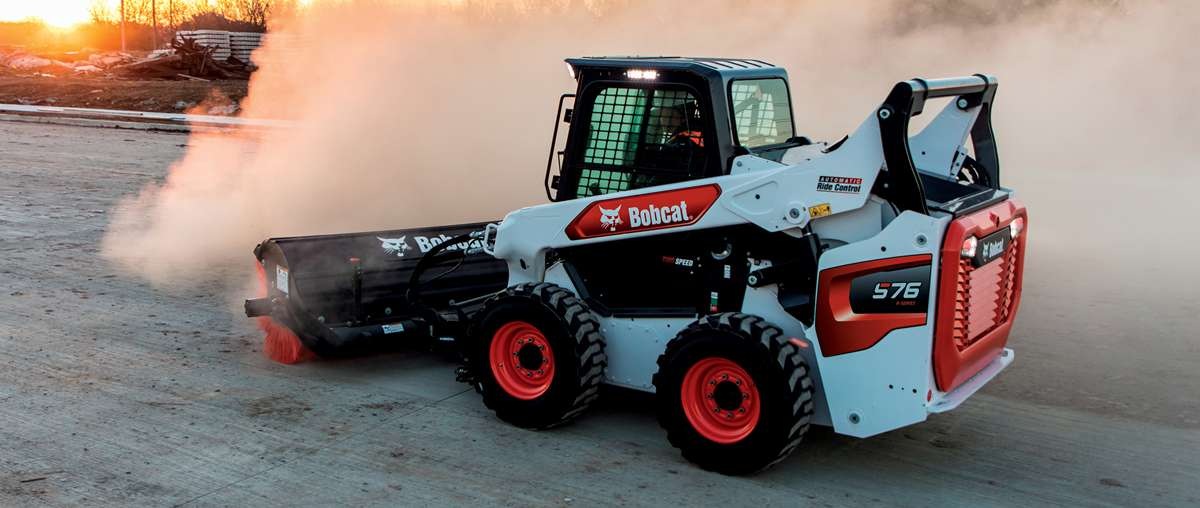 Bobcat Operator Using Skid-Steer Loader With Angle Broom To Clear Jobsite