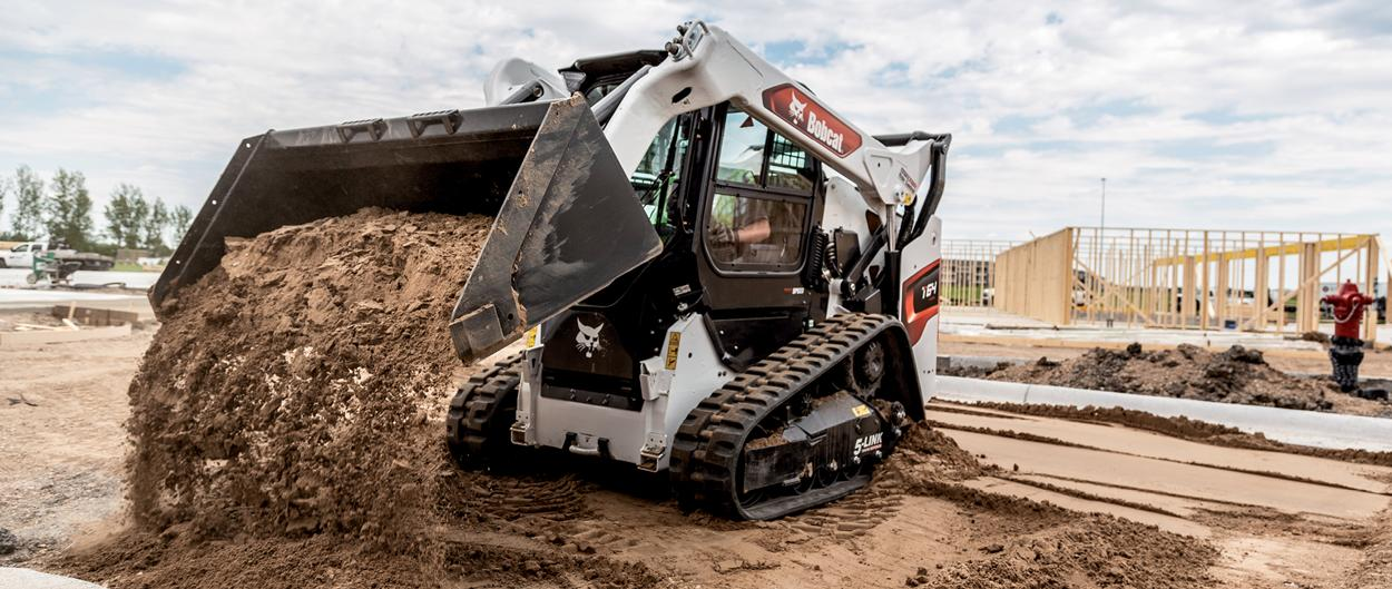 Operator Using Bobcat T64 Compact Track Loader With Bucket Attachment To Move Dirt On Construction Site