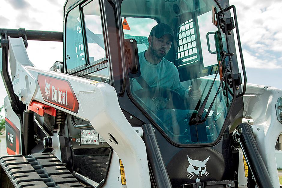 Operator Inside The Machine Cab Demoing Features Of A Bobcat Compact Track Loader
