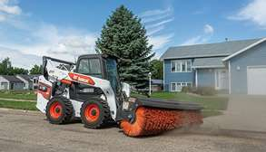 Bobcat R-Series S76 Skid-Steer Loader Sweeping Jobsite With Angle Broom Loader Attachment