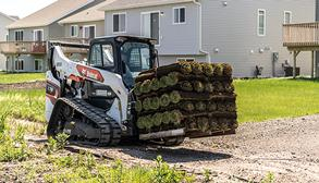 Landscaper Using Bobcat Compact Track Loader To Move Sod With Pallet Fork