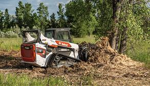 Operator Using Compact Track Loader With Root Grapple Loader Attachment To Remove Tree Roots
