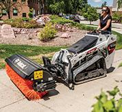 Groundskeeper Uses Mini Track Loader With Angle Broom Attachment To Clear Driveway