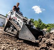 Landscaper Uses Mini Track Loader With Bucket Attachment To Move Dirt