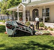Landscaper Unloads Bags Of Mulch From Mini Track Loader With Pallet Fork Attachment In Front Yard Of A Home
