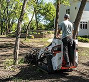 Homeowner Navigates Mini Track Loader With Soil Conditioner Attachment Between Trees