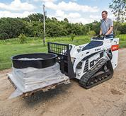 Bobcat MT85 mini track loader with pallet fork hauls materials.
