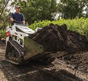 Bobcat MT85 mini track loader hauls dirt.