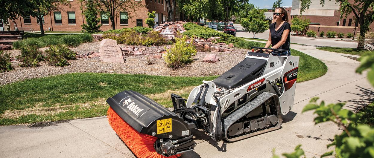 Groundskeeper Uses Mini Skid Steer With Angle Broom Attachment To Maintain Driveway Roundabout