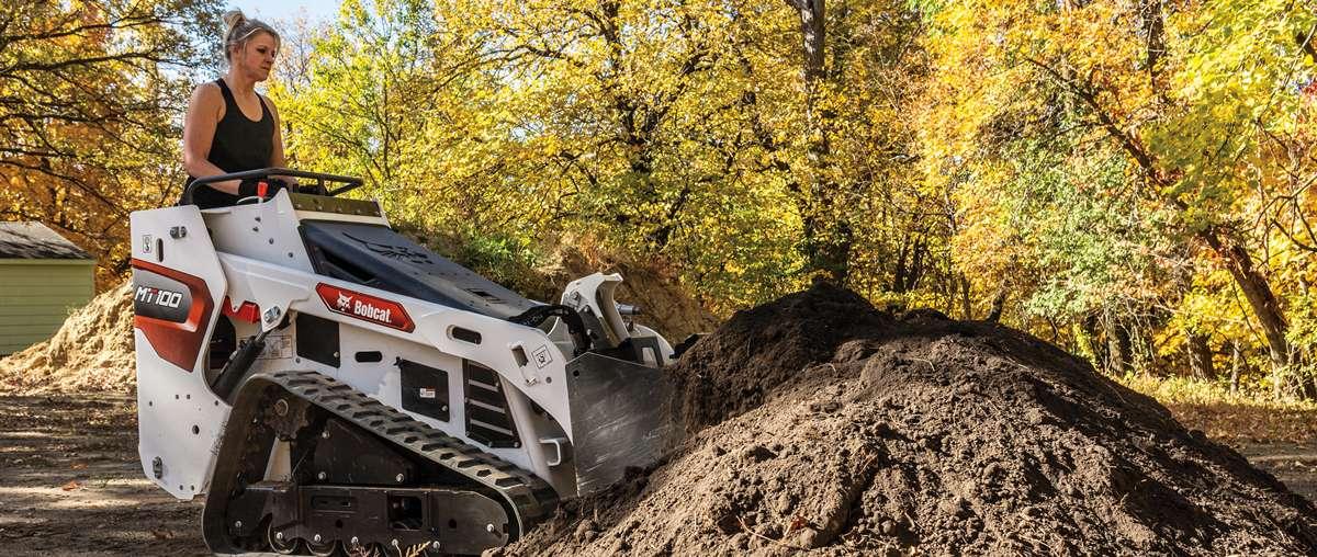 Mini Track Loader Operator Moving Large Mound of Dirt
