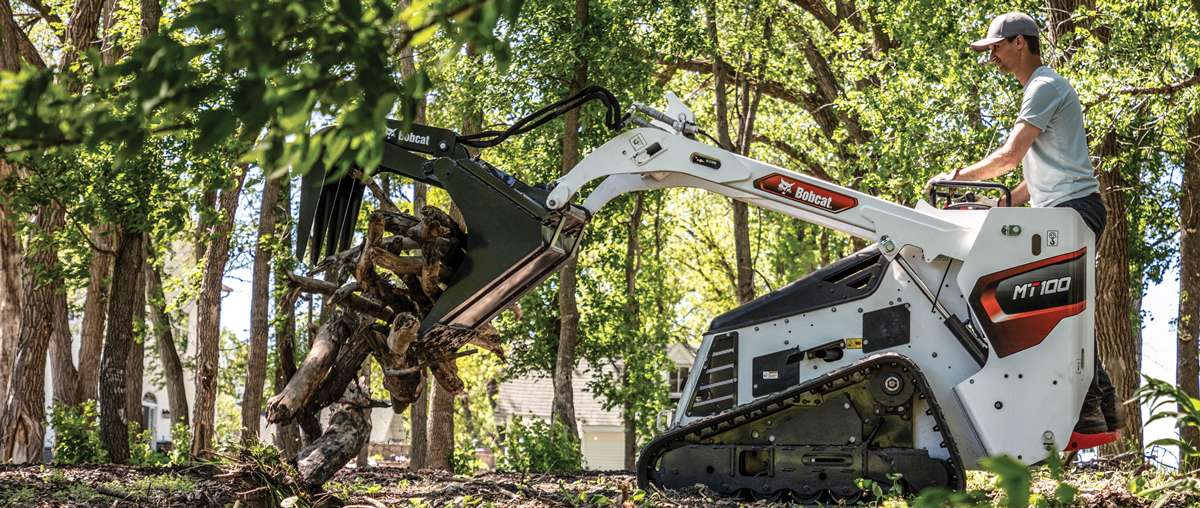 Mini Track Loader Operator Pulling Out a Tree Stump