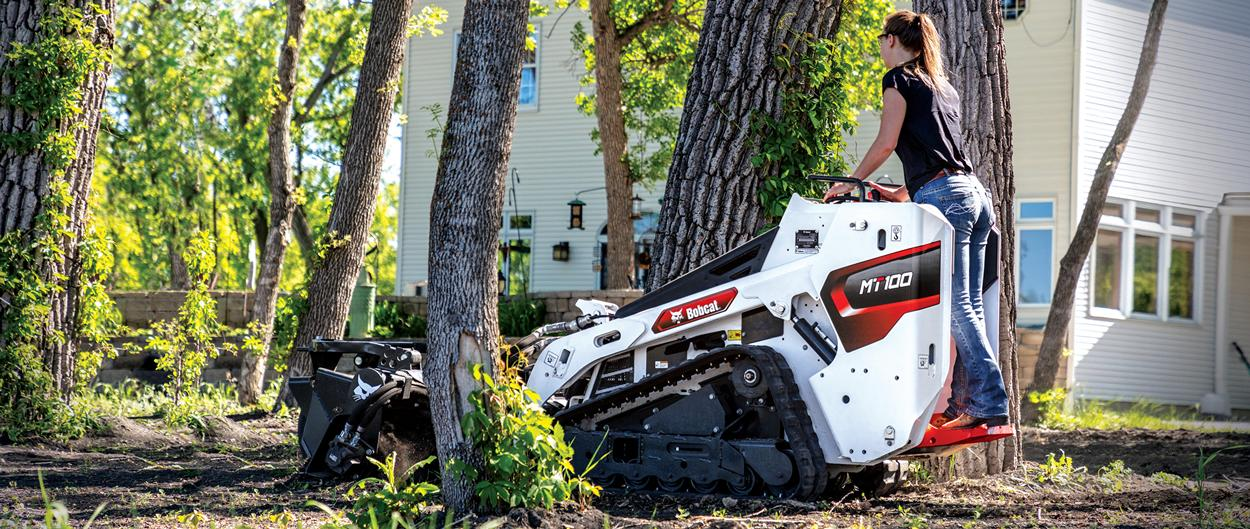 Homeowner Maneuvers Mini Track Loader Through Close Trees With Soil Conditioner Attachment