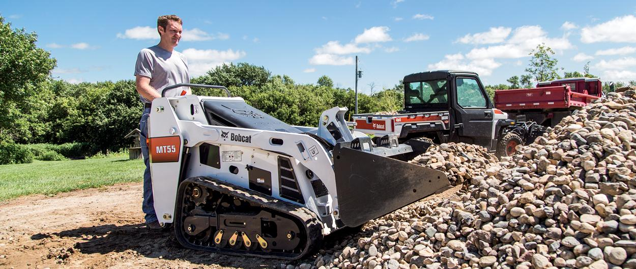 Landscaper Uses Bobcat MT55 Walk Behind Loader To Move Rocks From Pile