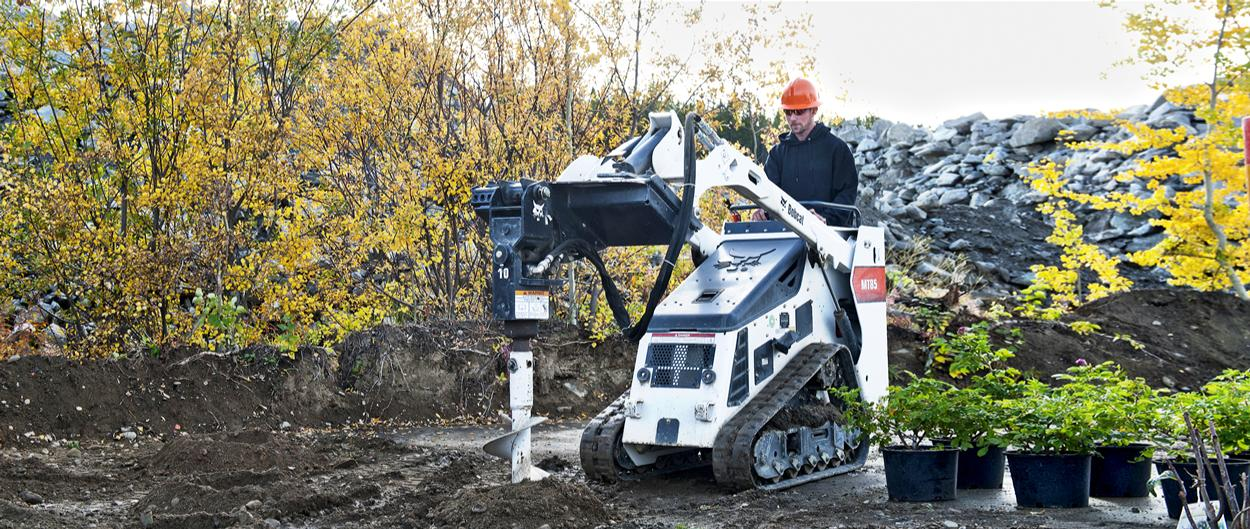 Bobcat MT85 mini track loader and auger attachment digging holes for planting trees and shrubs.