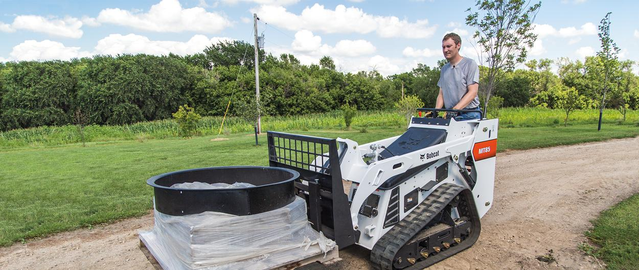 Bobcat mini track loader hauls rock in tight conditions.