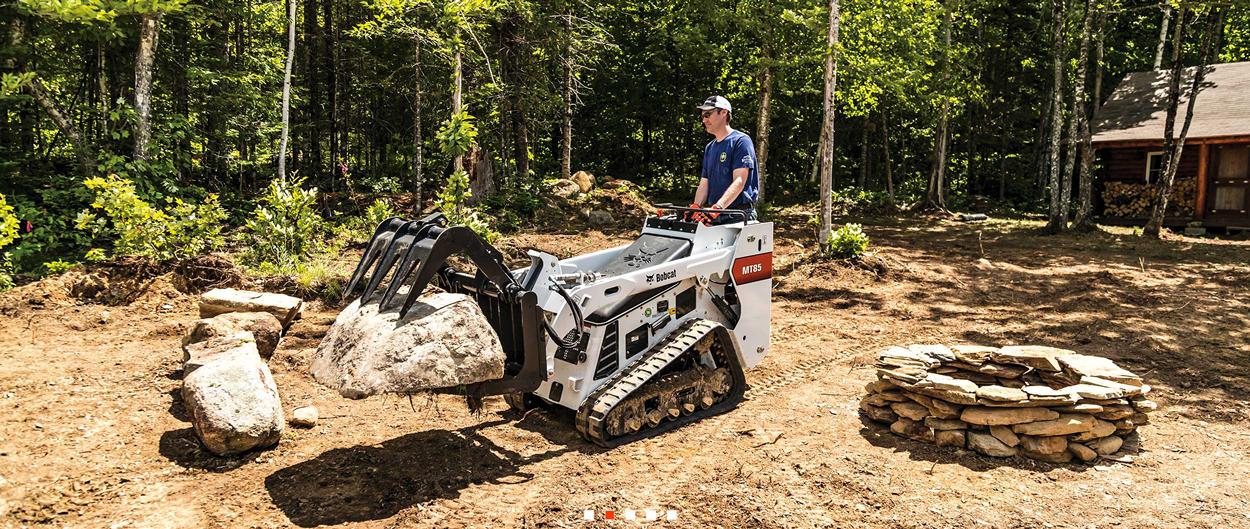 Bobcat MT85 mini track loader with grapple attachment moving a large rock.