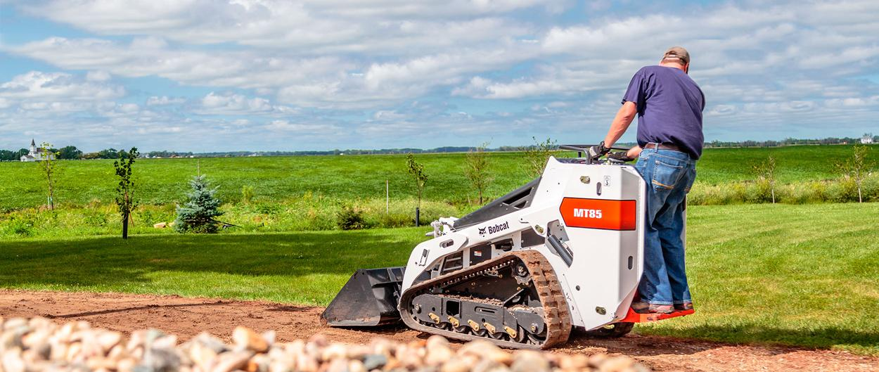 A Bobcat MT85 mini track loader navigates a gravel path.