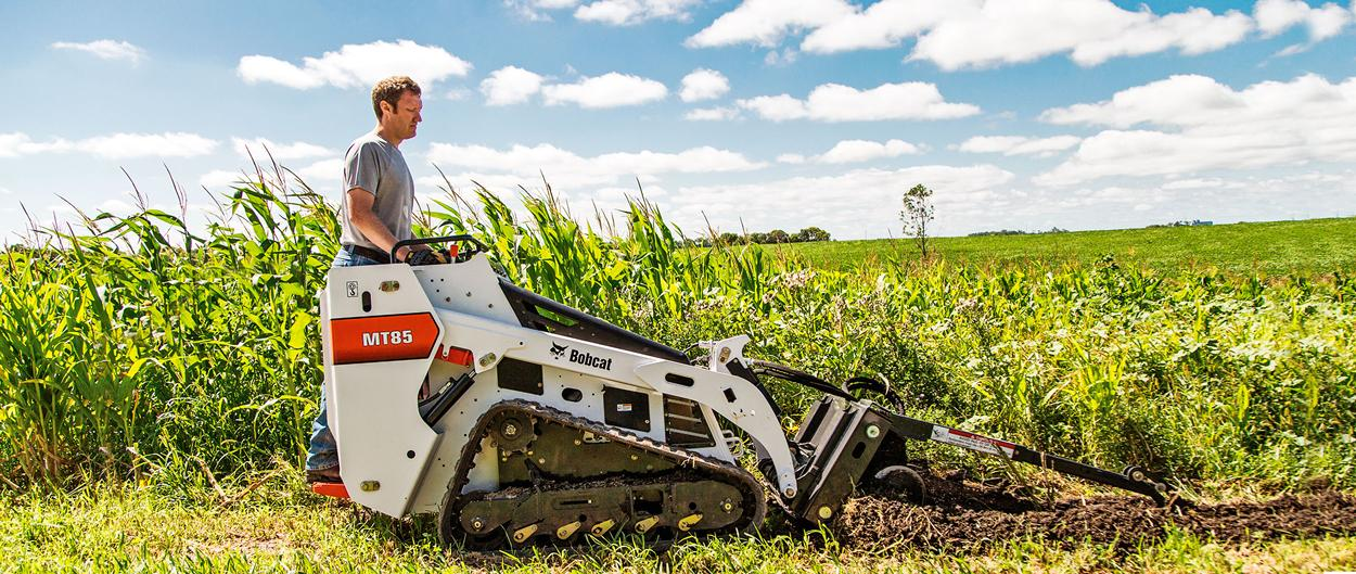 An MT85 mini track loader and trencher attachment dig a trench in a field.