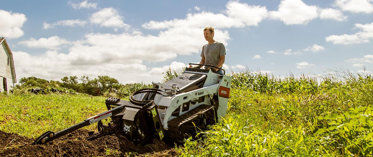 Bobcat MT85 mini track loader digs a trench with a trencher attachment.
