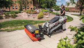 Landscaper Cleaning Path With Bobcat MT100 Mini Skid-Steer With Angle Broom Attachment