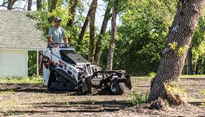 Homeowner Landscapes Garden With Mini Skid Steer And Soil Conditioner Attachment