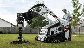 Landscaper Using Bobcat MT55 Mini Track Loader With Auger Attachment To Dig Hole In Lawn