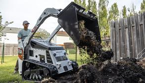 Landscaper Moves Dirt In Small Area With Bobcat Mini Track Loader With Bucket Attachment