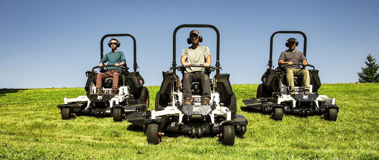 Multiple Operators Seated on Bobcat Zero-Turn Mowers Positioned on Grassy