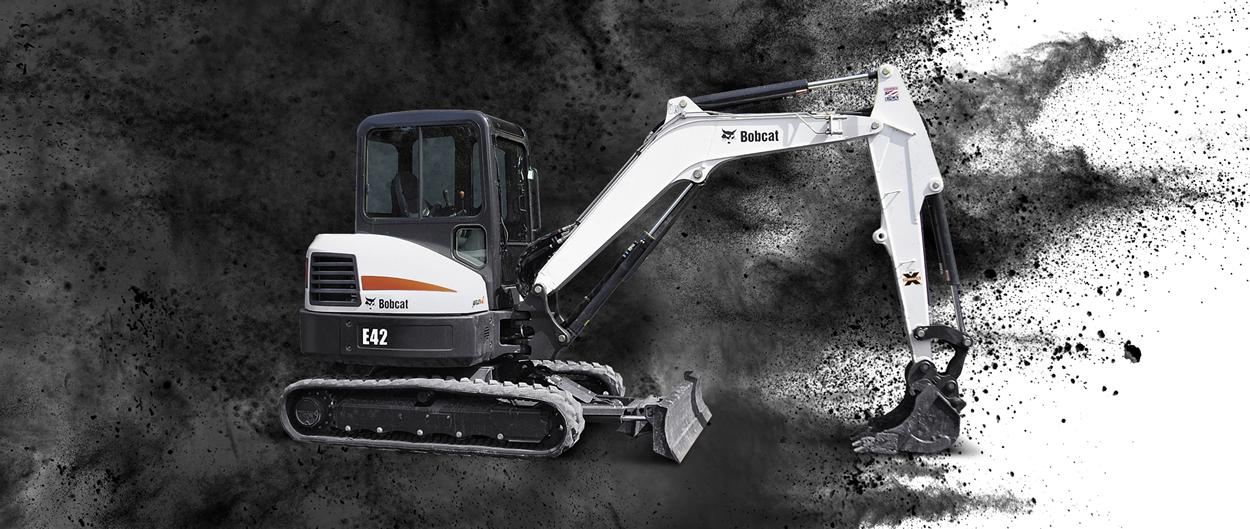 Bobcat E42 compact (mini) excavator and bucket attachment with a dirt background.