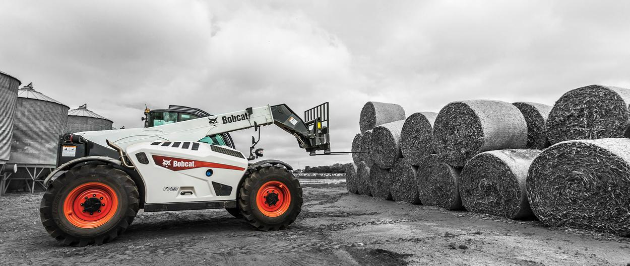 Bobcat V723 Telehandler With Grapple Attachment Moving Round Hay Bales On A Farm.