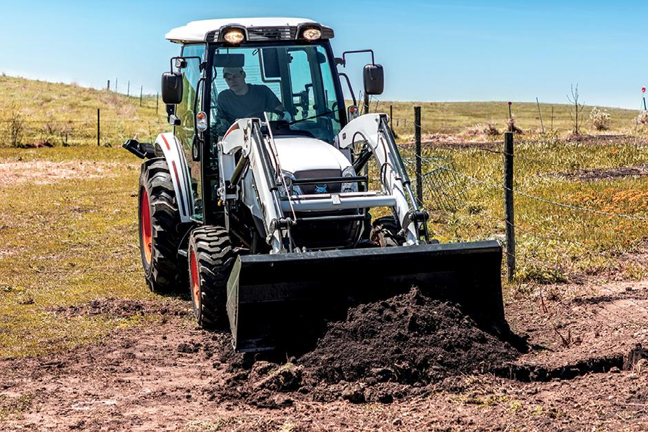 Operator Using Bobcat Compact Tractor with Front-End Loader To Move Dirt Along Fence Line