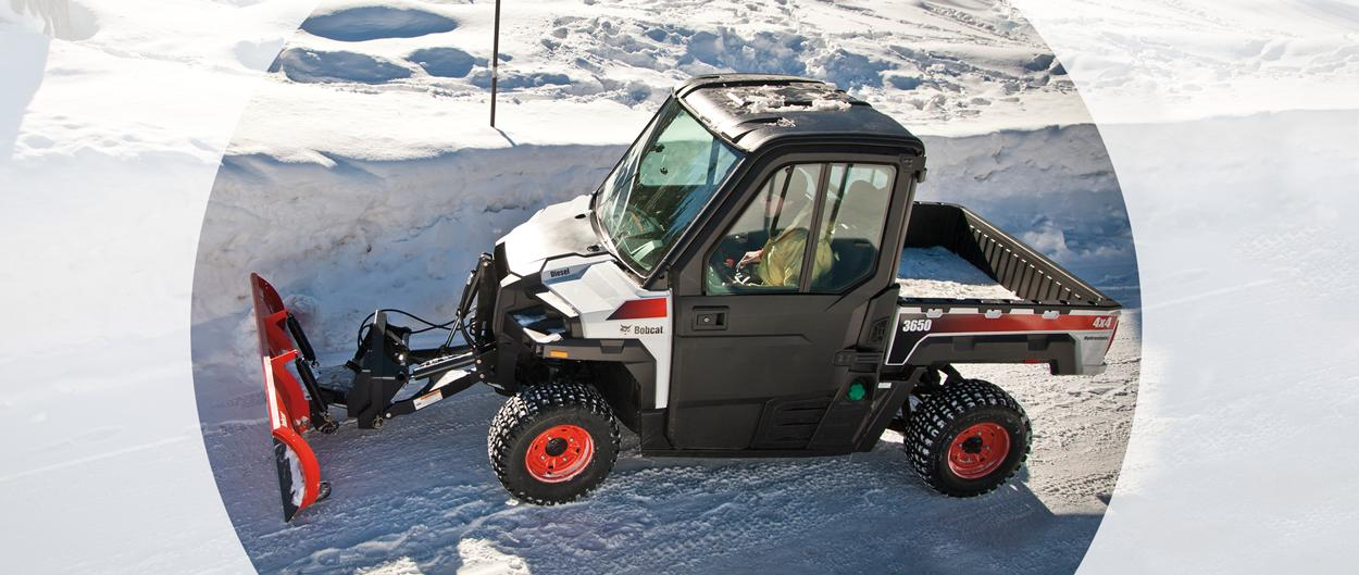 A Bobcat 3650 clears snow with the snow blade attachment.