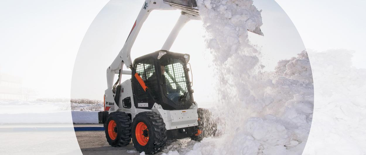 Bobcat S650 skid-steer loader and bucket attachment piling snow.
