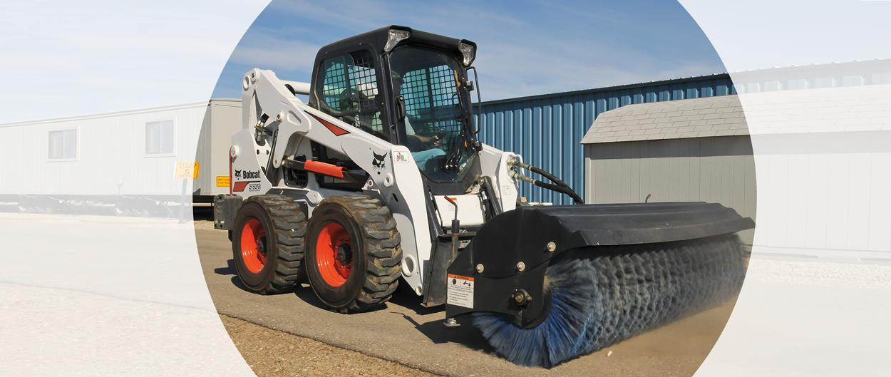 Bobcat S650 skid-steer loader and angle broom attachment cleaning a path