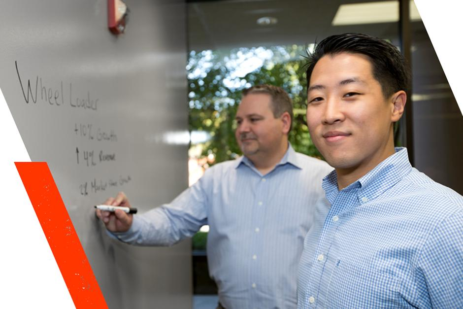 Two Engineering Students In The Bobcat Intern Program Write On White Board