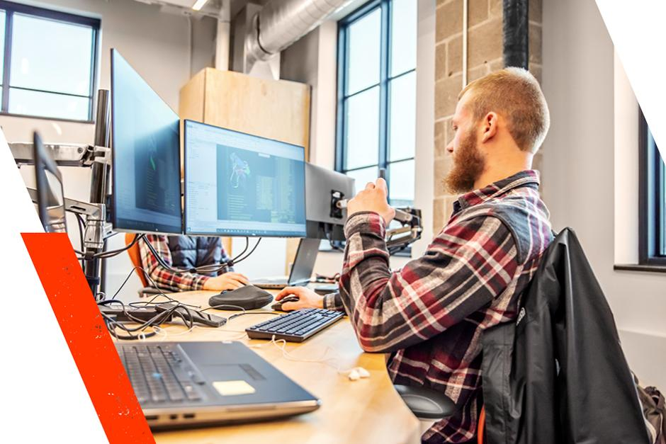 An Engineering Intern In The Student Development Program Works At His Desk Using Two Monitors