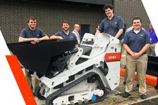 Interns In The Engineering Prototype Program Stand Side-By-Side Around A Bobcat MT85