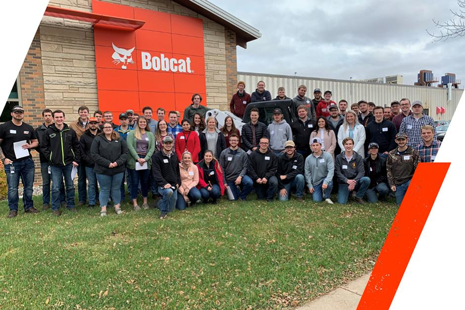 Group Photo Of Students Posing In Front Of The Bobcat Gwinner Factory Following Their Tour