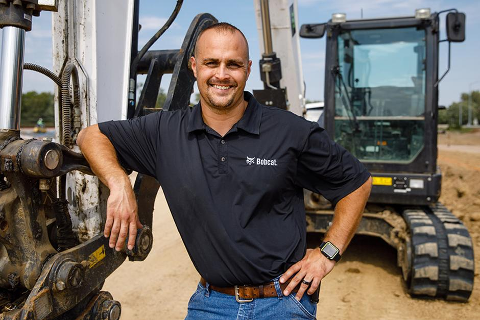 Bobcat Dealer Smiles for a Photo On A Jobsite Next To An Excavator